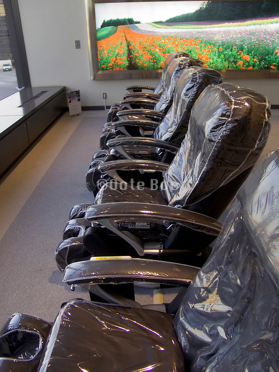 a row of empty massage chairs at an airport terminal