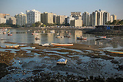 The large buildings of Mumbai can be seen encroaching on the fishing village.  The small fishing village of Machimaar Nagar struggles to hold on as the explosive growth of Mumbai begins to encroach on its space.