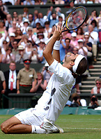 Roger Federer (Switzerland) drops to his knees in celebration of his Mens Singles Final victory over Mark Philippoussis (Australia) Wimbledon Tennis Championship, Day 13, 6/07/2003. Credit: Colorsport / Matthew Impey DIGITAL FILE ONLY