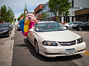 """28 JUNE 2020 - DES MOINES, IOWA: A participant in the Capitol City Pride Parade in Des Moines. Most of the Pride Month events in Des Moines were cancelled this year because of the COVID-19 pandemic, but members of the Des Moines LGBTQI community, and Capitol City Pride, the organization that coordinates Pride Month events, organized a community """"parade"""" of people driving through the East Village of Des Moines displaying gay pride banners and flags. About 75 cars participated in the parade.     PHOTO BY JACK KURTZ"""