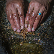 Finely grinded apricot kernels are sprinkled with water and pressed on a large heated stone. in a mortar. Banafsha making apricot oil by hand. In Shimshal, one of the remotest village in the Karakoram mountains, and the highest settlement in the Hunza and Gojal region.