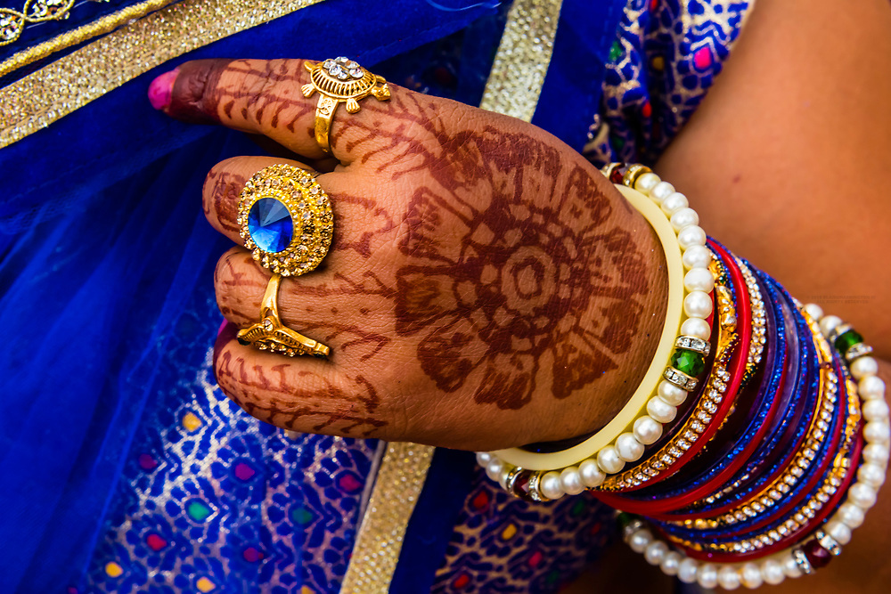 Veiled woman with Mehndi (Henna dye body art) on hands, Chhadi Mar Holi (local Holi celebration), Holi Festival (Festival of Colors), village of Gokul, near Mathura, Uttar Pradesh, India.