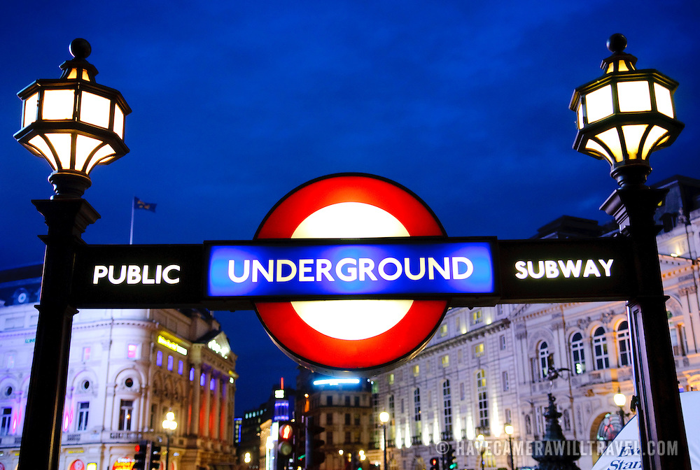 London Underground entrance and sign at Piccadilly Circus, at night with dark blue sky in the background. Editorial use only.