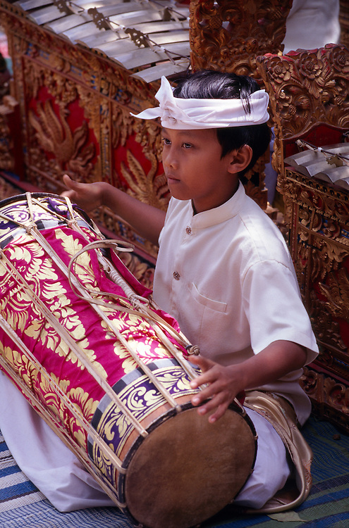 A Balinese boy plays a drum in a children's gamelan orchestra at a cultural performance at a school in the village of Peliatan, Bali, Indonesia