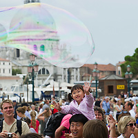 VENICE, ITALY - JULY 28:  A little girl enjoys a large soap bubble amoung the very crowded St Marks Square --------------------<br /> FOR LARGER RESOLUTION OR TO LICENCE THIS PICTURE: please contact us via e-mail at sales@xianpix.com or call our offices in Milan at (+39) 02 400 47313 or London   +44 (0)207 1939846 for prices and terms of copyright. First Use Only ,Editorial Use Only, All repros payable, No Archiving.© MARCO SECCHI
