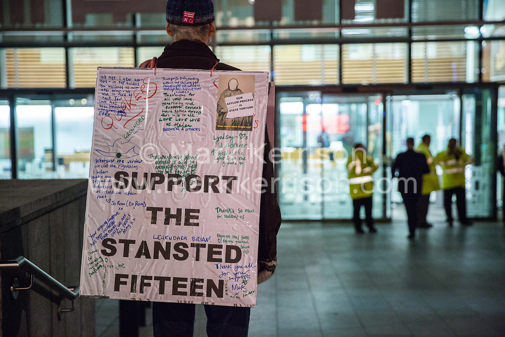 London, UK. 11th December, 2018. A man stands outside the Home Office in protest against the conviction the previous day using an anti-terrorism offence under the Aviation and Maritime Security Act 1990 of the Stansted 15 following non-violent direct action to try to prevent a Home Office deportation flight taking off from Stansted airport in March 2017. The judge directed the jury to disregard evidence put forward in their defence that their acts were intended to stop human rights abuses.
