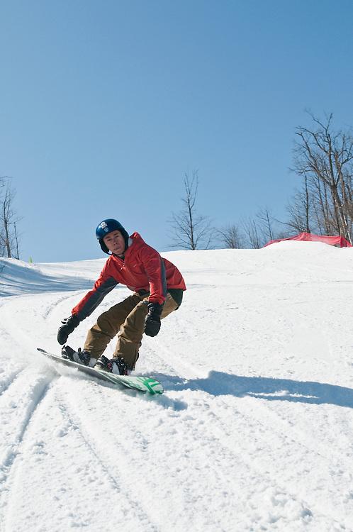 Snowboarder Jordan Hedlund at Marquette Mountain ski area in Marquette Michigan.