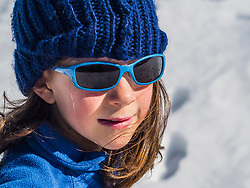 Girl wearing sunglasses and a blue knit cap on sunny day in the snow
