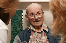 Elderly man and carers chatting; homecare for the elderly,