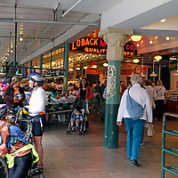 USA, Washington, Seattle. Cyclists at Pike Place Market, a Seattle landmark.