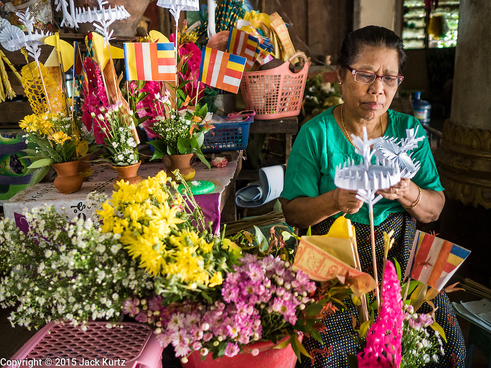 30 OCTOBER 2015 - TWANTE, MYANMAR:   A vendor makes offering baskets for people who want to make merit at the temple in the main entrance to the Shwe San Taw Pagoda (Paya) in Twante, also spelled Twantay. The pagoda was established more than 2500 years ago, although constantly rebuilt and renovated. According to Burmese history and local legend, the pagoda houses eight hairs from Gautama, the historical Buddha. PHOTO BY JACK KURTZ