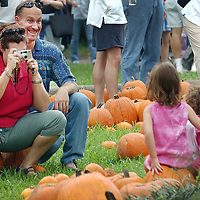 Gordon Fox makes a face trying to get his daughters Hannalee, 4, and Sararose, 2, to smile as his wife Lesley takes a picture of them in the pumpkin patch at the Discovery Center in Bellaire, 10/12/02.