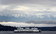 Viewed from Alki Beach in W. Seattle, a ferry heading east glides past Olympic Mountains struggling to break out of cloud cover. (Ken Lambert / The Seattle Times)