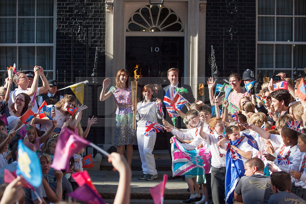 © licensed to London News Pictures. London, UK 26/07/2012. David and Samantha Cameron posing with Kate Nesbitt who carries the torch to Downing Street. Photo credit: Tolga Akmen/LNP