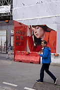 A man holding his phone, walks past the temporary construction hoarding outside Arthur Stanley House, on 12th July 2021, in London, England.