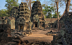 Back courtyard of Banteay Kdei temple with early morning shafts of dawn light illuminating two small temples,