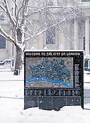 A City of London map and information sign outside St Pauls Cathedral, covered in snow. London, UK