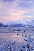 Turnagain Arm in winter Alaska.  Weak winter light illuminates a peak in the Chugach Mountains. Chunks of sea ice float in the waters of Turnagain Arm.  This area is surrounded by the Chugach National Forest.