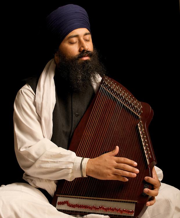 Punjab Singh playing a swarmandal.