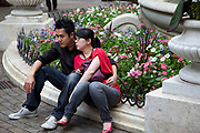 Young Asian couple relaxing together in Leicester Square, London. There are a lot of Chinese in this area as it is very near to Chinatown.