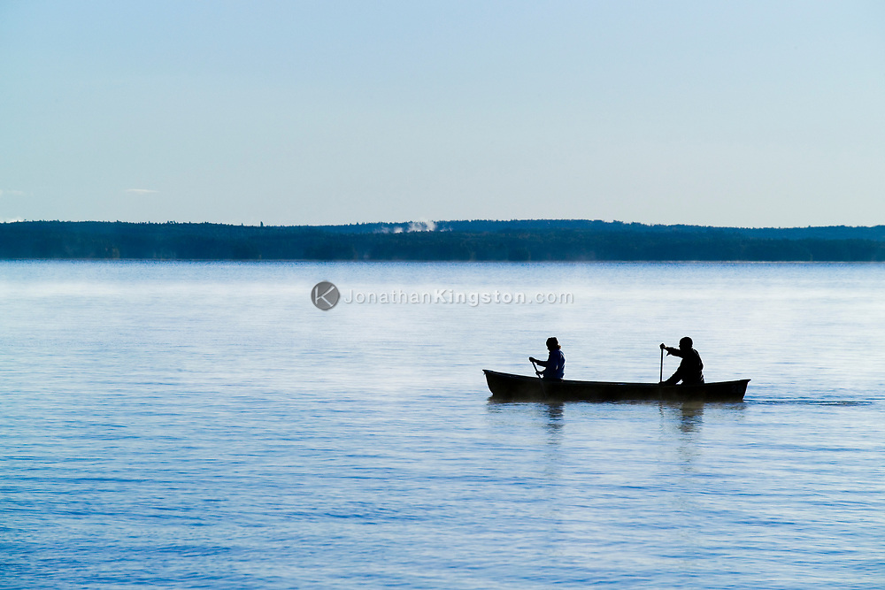 Two canoeists ply the waters in the morning mist of Sebago Lake in Maine. (Model Released)