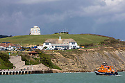 The Royal National Lifeboat Institution RNLI Dover Life boat 17-09  arrives into Folkestone near the Folkestone is an Art School banner, attached to Folkestone's most prominent Martello Tower on the east cliff. The banner has been designed by the artist Bob and Roberta Smith as part of the 2017 Folkestone Triennial. Folkestone, Kent.