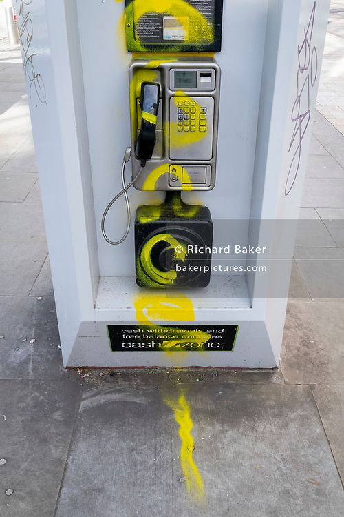 A public BT landline phone kiosk has been vandalised by the spraying of yellow aerosol paint over its handset and keypad on the Southbank in Waterloo, on 11th March 2021, in London, England.