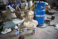 Color film photograph of a bust surrounded by tools and objects inside a workshop of Dai Bai bronze casting craft village, Bac Ninh Province, Hanoi outskirts, Vietnam, Southeast Asia