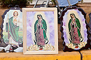 """Dec. 12, 2009 -- PHOENIX, AZ: Religious pictures, including some of the Virgin of Guadalupe, for a sale during a procession to honor the Virgin of Guadalupe at St. Catherine of Siena Catholic Church in Phoenix, AZ. Most of the members of the church are Hispanic and Dec. 12, Virgin of Guadalupe Day, is one of the church's most important holy days. The Virgin of Guadalupe appeared to Juan Diego, a Mexican peasant, on Dec 9, 1531, on a hillside near Mexico City. She is the """"Queen of Mexico"""" and """"Empress of the Americas"""" and revered throughout Latin America.  Photo by Jack Kurtz"""
