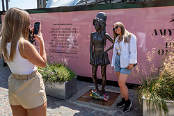 © Licensed to London News Pictures. 23/07/2021. LONDON, UK.  A woman has her photo taken with the statue of Amy Winehouse by sculptor Scott Eaton in Stables Market in Camden Town on the tenth anniversary of the late singer's death.  Photo credit: Stephen Chung/LNP