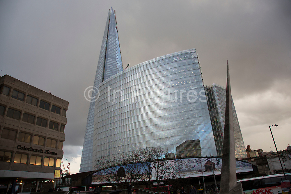 The Shard looming over the city on cloudy and stormy day in London, UK.  The Shard, also referred to as the Shard of Glass, Shard London Bridge and formerly London Bridge Tower, is an 87-storey skyscraper in London that forms part of the London Bridge Quarter development.