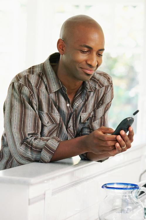 Smiling man using mobile phone at home