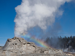 North America, United States, Wyoming, Yellowstone National Park, Upper Geyser Basin, rainbow and steam at Castle Geyser as it erupts in winter