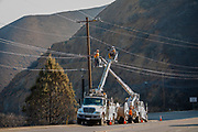 Utility workers fixing downed power lines along Kanan Dume Road. The Woolsey wildfire started on November 8, 2018 and has burned over 98,000 acres of land, destroyed an estimated 1,100 structures and killed 3 people in Los Angeles and Ventura counties and the especially hard hit area of Malibu. California, USA