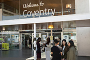 Group of young people chatting outside Welcome to Coventry sign outside the mainline railway station in the UK City of Culture 2021 on 23rd June 2021 in Coventry, United Kingdom. The UK City of Culture is a designation given to a city in the United Kingdom for a period of one year. The aim of the initiative, which is administered by the Department for Digital, Culture, Media and Sport. Coventry is a city which is under a large scale and current regeneration.