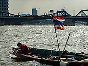 14 OCTOBER 2015 - BANGKOK, THAILAND: A spotter sluices things brought up from the river bottom while the diver he works with is in the Chao Phraya River in Bangkok. Divers work in two man teams on small boats in the Chao Phraya River. One person stays in the boat while the diver scours the river bottom for anything that can be salvaged and resold. The divers usually work close to shore because the center of the river is a busy commercial waterway with passenger boats and commercial freight barges passing up and down the river all day long. The Chao Phraya is a dangerous river to dive in. It's deep, has large tidal fluctuations, is fast flowing and badly polluted. The divers make money only when they sell something.    PHOTO BY JACK KURTZ