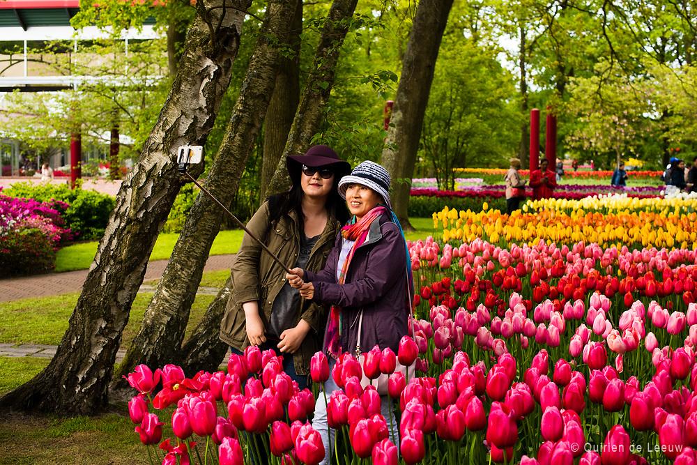 Toeristen maken een selfie tussen de tulpen in het Keukenhof park in Lisse