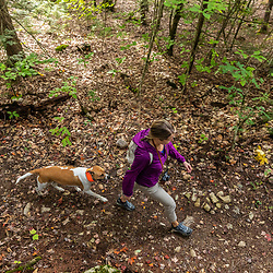 A woman and her dog on a hike in the Raymond Community Forest in Raymond, Maine. Fall.