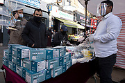 Face mask seller as Londoners from the mainly Bangladeshi Asian community await the second coronavirus national lockdown it's business as usual at Whitechapel Market with people out and about, some wearing face masks and some not, on what will be the last few days of normality before a month-long total lockdown in the UK on 2nd November 2020 in London, United Kingdom. The three tier system in the UK has not worked sufficiently, to suppress the virus, and there have have been calls by politicians for a 'circuit breaker' complete lockdown to be announced to help the growing spread of the Covid-19.