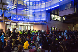 London, UK. 11 October, 2019. Climate activists from Extinction Rebellion, two of which on a glass parapet, block the main entrance to the BBC's New Broadcasting House on the evening of the fifth day of International Rebellion protests. They were demanding that the broadcaster 'tell the truth' regarding the climate emergency.