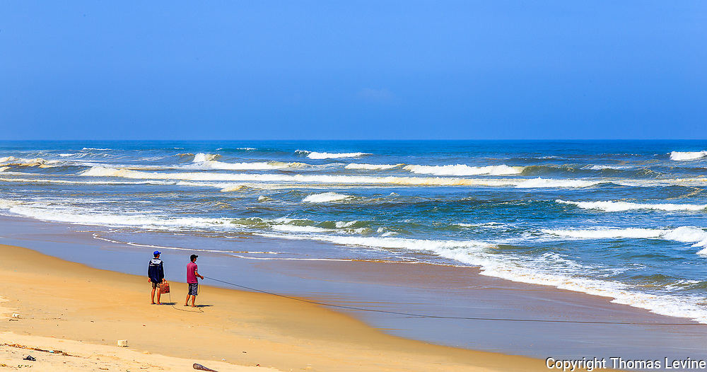 Two fisherman pulling in a line at Tan Thanh Beach, Vietnam.
