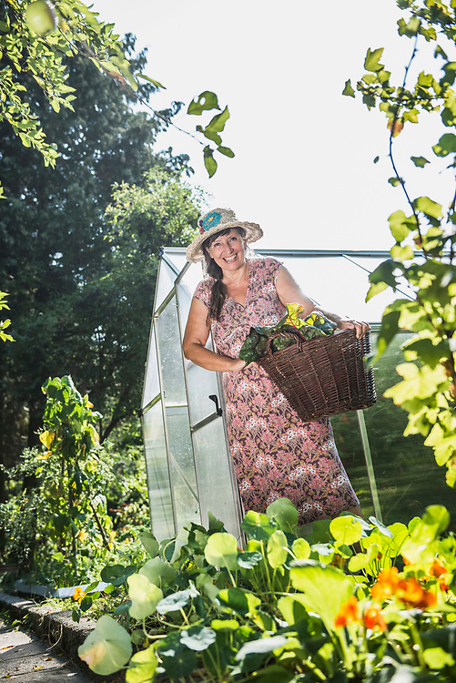 Woman with a basket of chard leaves in garden, Altoetting, Bavaria, Germany