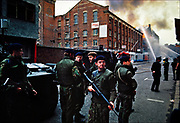 British Army sharpshooters surround commanders of anti-terrorism troops at the site of a terrorist bombing of a children's clothing factory in Belfast during the civil war in Northern Ireland.  This photograph was taken in October 1976.  © Steve Raymer / National Geographic Creative