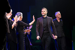 """© Licensed to London News Pictures . 12/01/2016 . Salford , UK . Writers GARY BARLOW (c) and TIM FIRTH (r) make a surprise appearance and Barlow performs in front of the audience at the Lowry Theatre ,  during the opening week of """" The Girls """" , a musical they wrote based on the story """" Calendar Girls """" , about a group of Women's Institute members in Yorkshire , who made a nude calendar . Photo credit : Joel Goodman/LNP"""