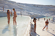 Tourists having fun at the pools at pamukkale. The hard, white mineral deposits, which from a distance resemble snow, are caused by the high mineral content of the natural spring water which runs down the cliff and congregates in warm pools on the terraces. This is such a popular tourist attraction that strict rules had to be established in order to preserve its beauty, which include the fact that visitors may no longer walk on the terraces. Those who want to enjoy the thermal waters, however, can take a dip in the nearby pool, littered with fragments of marble pillars.