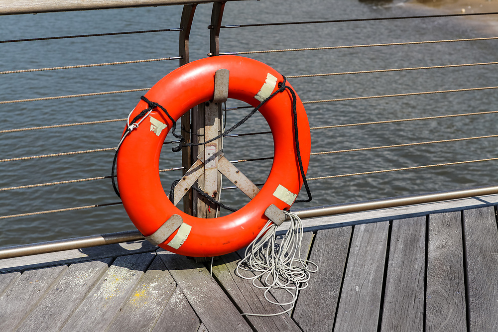 A bright orange lifesaver with a rope against a fence on a dock at water.