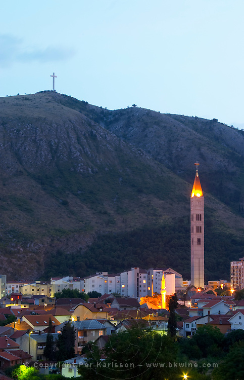 View over the city at sunset. Mosque minarets. Franciscan Monastery and church. Hill with a cross on the hilltop in the background Historic town of Mostar. Federation Bosne i Hercegovine. Bosnia Herzegovina, Europe.
