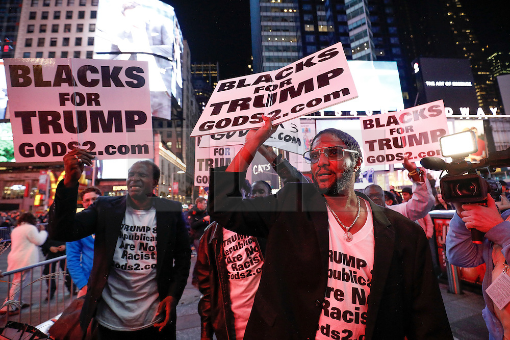 """© Licensed to London News Pictures. 09/11/2016. New York City, USA. A group of men holding signs reading """"BLACKS FOR TRUMP"""", react to news that Donald Trump looks likely to be elected as the next president of the United States, while gathering in Times Square, New York City, on Wednesday, 9 November. Photo credit: Tolga Akmen/LNP"""