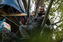 Aylesbury Vale, UK. 6th October, 2020. Daniel Marc Hooper, better known as Swampy, joins fellow anti-HS2 tree protectors in and around a makeshift tree house about sixty feet above ground at a wildlife protection camp in ancient woodland at Jones' Hill Wood. The Jones' Hill Wood camp, one of several protest camps set up by anti-HS2 activists along the route of the £106bn HS2 high-speed rail link in order to resist the controversial infrastructure project, is currently being evicted by National Eviction Team bailiffs working on behalf of HS2 Ltd.