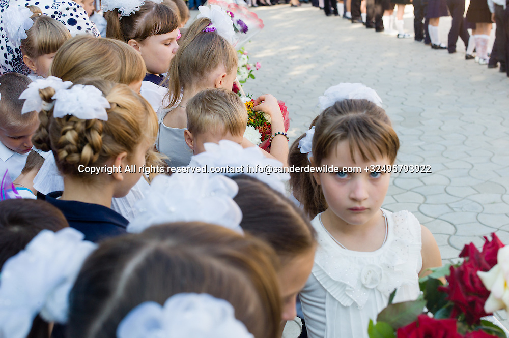 20150901 Moldova, Transnistria,Pridnestrovian Moldavian Republic (PMR) Tiraspol.Day of knowledge. First of september schools start and kids are dressed up in white and black. They brought flowers for their teachers.girl looks i camera, listening to boring speeches.